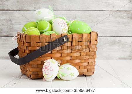 Easter greeting card with colorful easter eggs basket in front of wooden wall