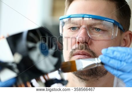 Close-up Man Goggles Mends Mechanical Part Device. Replacement Thermal Paste Processor, Lubrication
