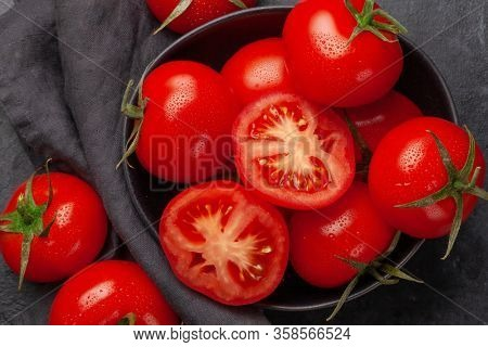 Fresh ripe tomatoes in bowl on stone table. Top view
