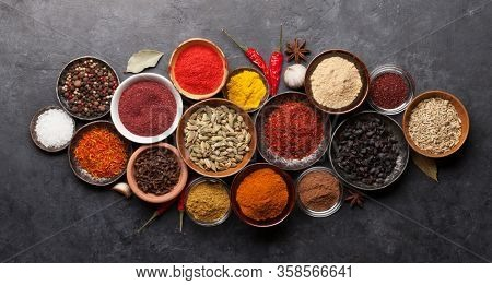 Various spices in bowls on dark stone table. Indian cuisine. Top view flat lay