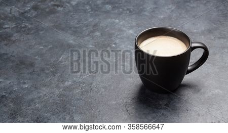 Coffee cup on dark stone table. With copy space