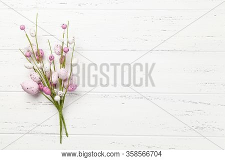 Easter greeting card with colorful easter eggs decor on wooden background. Top view flat lay with space for your greetings