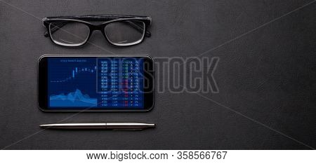 Office workplace table with smartphone with stock market analytics app, glasses and supplies. Flat lay. Top view with space for your goals