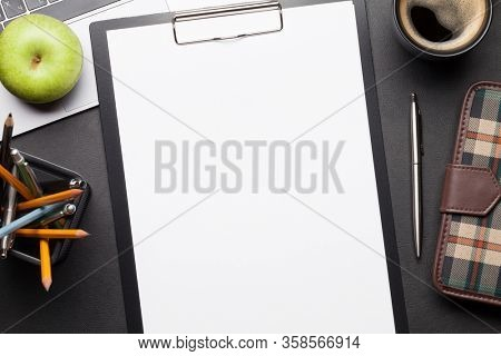 Office desk table with laptop, supplies and coffee. Dark workspace tabletop with blank sheet for copy space. Top view flat lay
