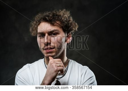 Close-up Portrait Of A Young Handsome Male Model Posing On A Grey Background In A Dark Studio, Weari