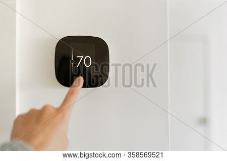 Thermostat indoor smart home in house system for temperature. Winter heating energy efficient automation digital touchscreen wall hand touching device to adjust heating in living room. IoT domotics.