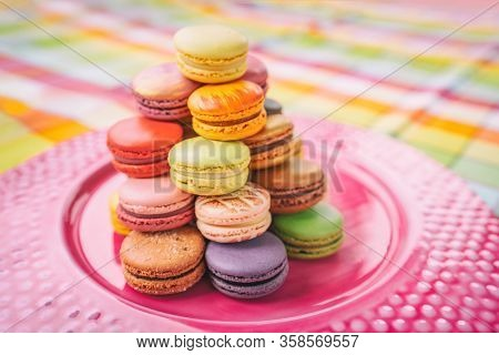 Macarons tower on dessert plate at home. Cute retro vintage pink plate on checkered tablecloth easter table decoration home kitchen. Assortment of pastel colored macaron of different flavors.