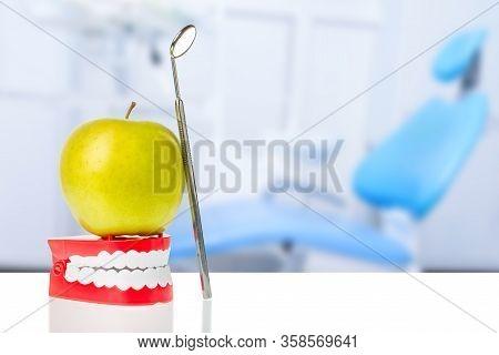 Dental Mirror Near Green Apple On Human Jaw Model Against Dental Chair Background. Oral Dental Hygie