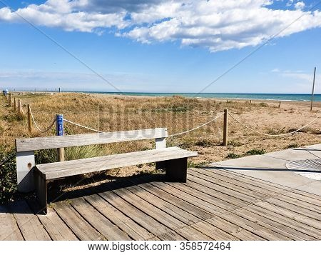 Empty Wooden Bench On The Beach, Views Of The Sea, Castelldefels, Spain