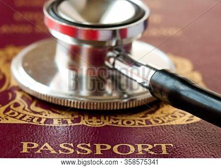International travel restrictions to combat coronavirus concept image.   Passport and stethoscope.