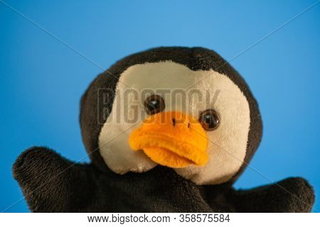 Soft Puppet Toy On Blue Background. Concept Of Puppet Show. Close-up Of Puppet Penguin.