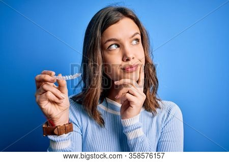 Young blonde girl holding dental orthodontic clear aligner over blue isolated background serious face thinking about question, very confused idea