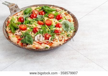 Fresh Raw Pizza With Mushrooms, Cherry Tomatoes , Basil And Parmesan In A Round Pan On A White Backg