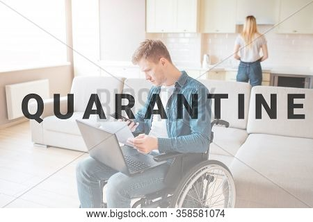 Young Busy Man With Disability Sitting On Wheelchair. Hold Laptop On Knees. Young Woman Stand Behind