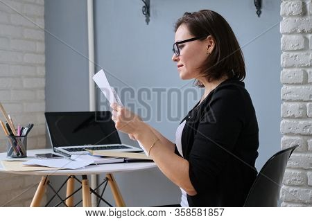 Mature Woman Sitting At Home At Desk With Laptop, Received An Envelope With Letter, Smiling Female R