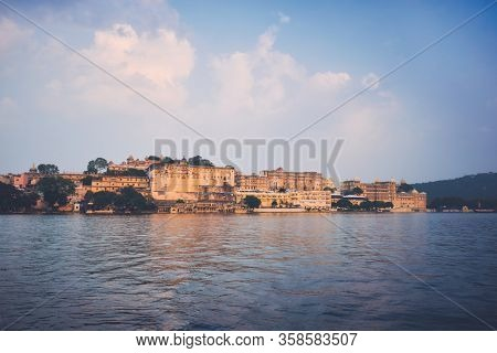 View of famous romantic luxury Rajasthan indian tourist landmark - Udaipur City Palace on sunset with cloudy sky. Udaipur, Rajasthan, India
