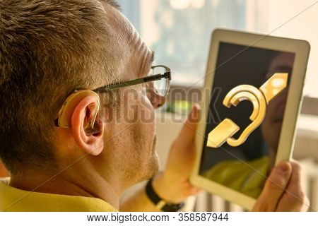 Man wearing deaf aid in ear with tablet showing deaf sign an the display. Concept of using tablets and smartphones by deaf and with hearing impairment people