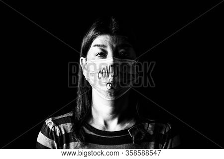 Woman with surgical mask. Biohazard and COVID-19, aka Coronavirus symbol. Pandemic or epidemic and scary, fear or danger concept. Black and White. Black Background
