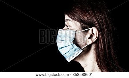 Woman with surgical mask. Pandemic or epidemic and scary, fear or danger concept. Protection for biohazard like COVID-19 aka Coronavirus. Close-up profile  portrait. Black Background.