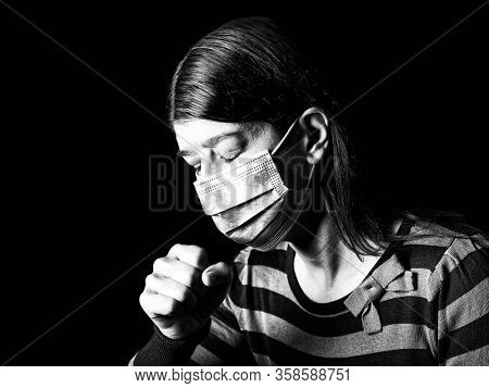 Woman with surgical mask sneezing or coughing. Pandemic or epidemic and scary, fear or danger concept. Protection for biohazard like COVID-19 aka Coronavirus. Black Background. Black and White