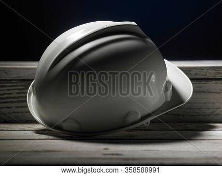 Safety first concept white hard safety wear helmet hat - Engineer worker helmet on wooden background.