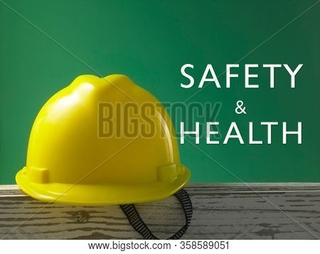 Safety first concept yellow hard safety wear helmet hat -with text safety and health