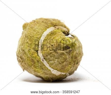 Chewed and broken tennis ball against white background