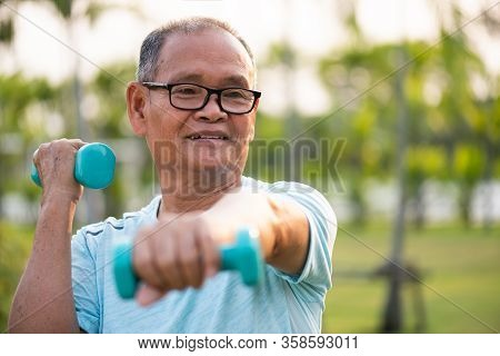 Asian Old Man Doing Physical Exercise Outdoor With Dumbbells. Be Healthy And Strong, Work On The Mus