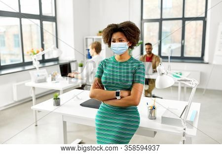 business and people concept - african american woman with smart watch wearing protective medical mask for protection from virus disease at office