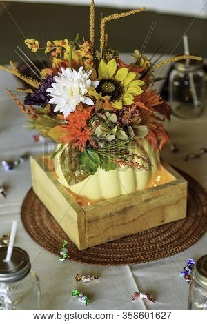 Table Decorated With A Centerpiece, Silverware And Drink Jars In Fall Colors Suitable For A Wedding,