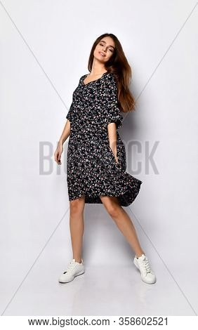 Pretty Brunette With Long Hair In A Black Wide Dress With Floral Print And White Sneakers. She Is Sm