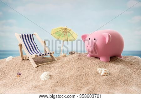 Piggy bank on beach vacation with deck chair and sunshade concept for finance and travel