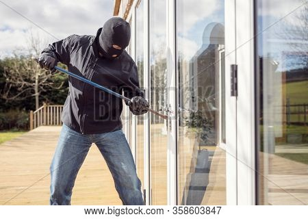Burglar or thief breaking into a home through window with a crowbar