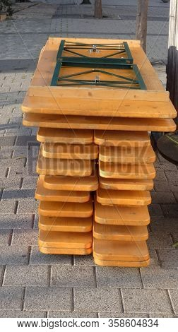 Pile Of Wooden Folding Tables And Benches In Village Square