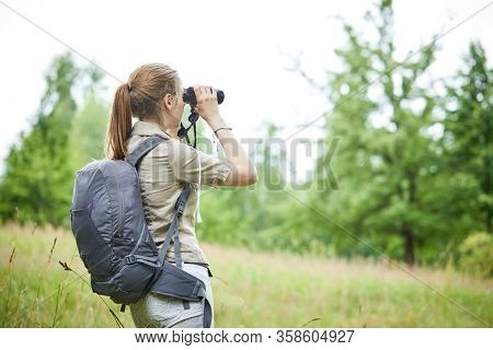 young woman with binoculars outdoor