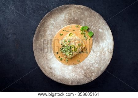 Gourmet fried skrei cod fish in Thai curry with chili and sprouts as top view on a modern design plate with copy space