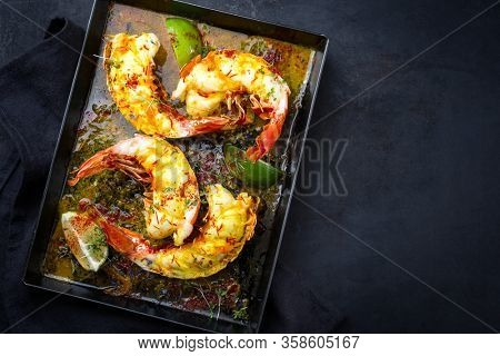 Traditional barbecue spiny lobster tail sliced and offered with saffron lemon sauce as top view on a metal tray with copy space right