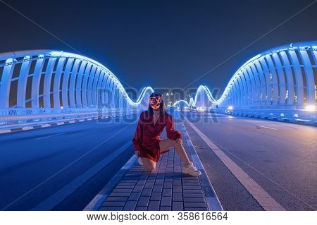 Woman With Lighting Neon Glow Mask On Meydan Bridge And Street Road Or Path Way On Highway In Dubai