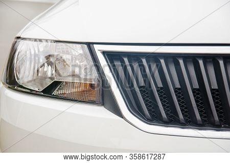 Photo Of A Headlight Of A Car. Car Headlight And Radiator Grill