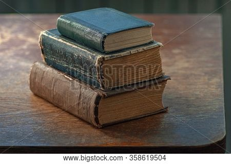 A Stack Of Old Shabby Books Lies On An Old Shabby Wooden Table. Close-up. Warm Colors.