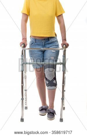 Woman With Walking Frame And Knee Orthosis Isolated On White Background