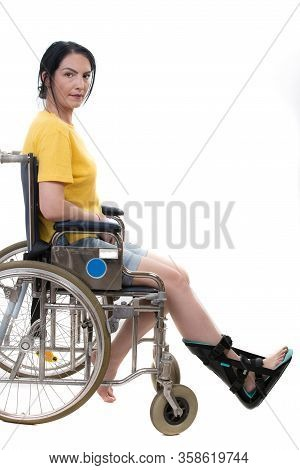 Casual Mid Adult Woman In Wheelchair With Foot Orthosis Isolated On White Background
