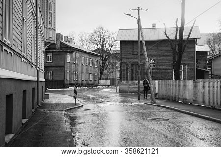 A Young Woman Walks Into A Crossing By The Old Wooden Buildings At Tallinn, Estonia. The Spring Is C