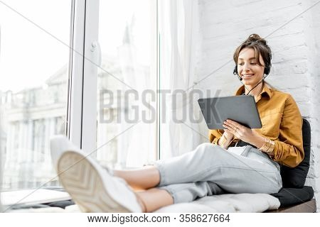 Young Woman With A Headset Working Online On A Digital Tablet While Sitting On The Window Sill At Ho