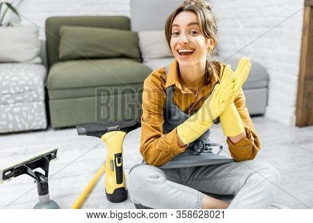 Portrait Of A Young And Cheerful Housewife Dressed For Work Sitting With Cleaning Tools On The Floor