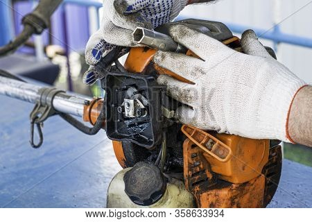 A Master In Working Gloves Repairs The Engine Of An Old Gas Trimmer And Unscrews The Spark Plug With