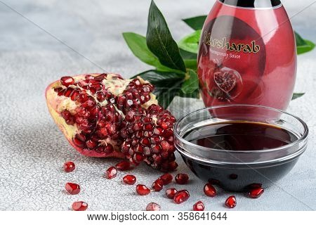 Glass Bottle And Saucer Of Pomegranate Sour Sauce With Fresh Ripe Pomegranate Fruits With Resolution