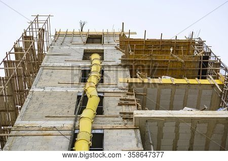 The Process Of Building A Residential Building. Scaffolding, Yellow Chute, Safe Waste Disposal. Open