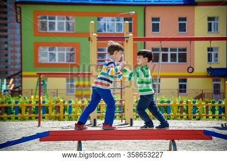 Two Little School And Preschool Kids Boys Playing On Playground Outdoors Together. Children Having C