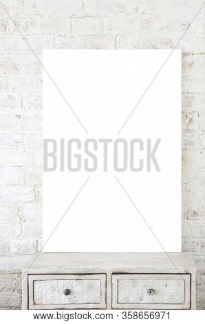 White Blank Poster Placed On Vintage Shabby Drawer Cabinet Against White Brick Wall